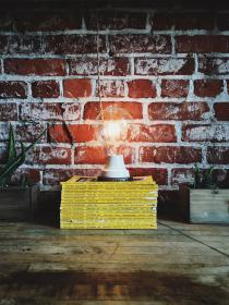 light bulb on a stack of yellow books in front of a brick wall