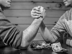 two guys armwrestling and some money laying on the table