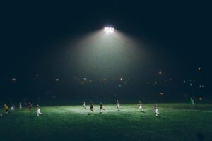 Two teams playing soccer under a big light at night