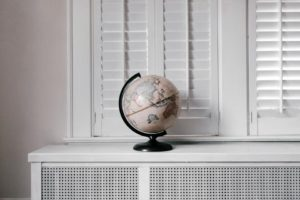 A window with with a world globe standing on the window shield