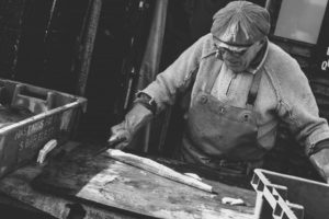 Black and white photo of man doing woodwork