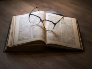 A book with a pair of glasses on