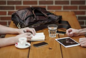 Two people having a meeting. Only the hands and the table are shown. On the table, there are one coffee cup, one glass of water, one phone, one tablet, a brown weekend bag and a notepad