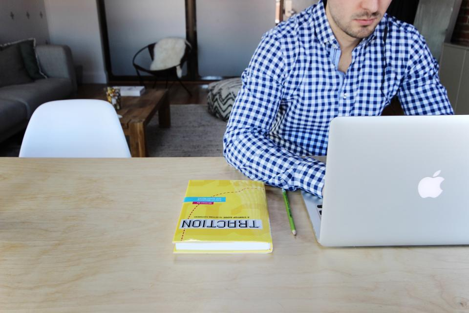 startup employee sitting with his Macbook Pro and a Book that says Traction