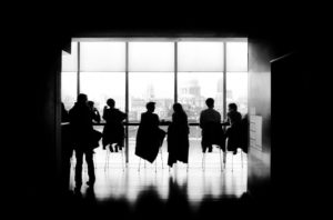 Six people sitting right in front of a panorama window with backlight